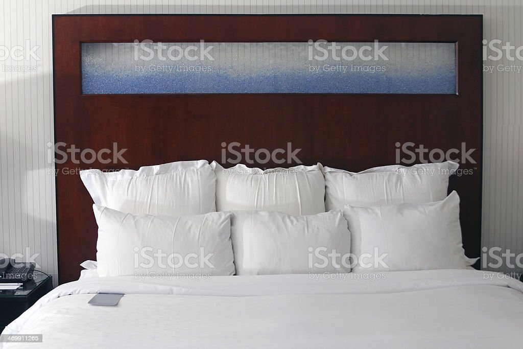 Hotel bed with pillows and phone royalty-free stock photo