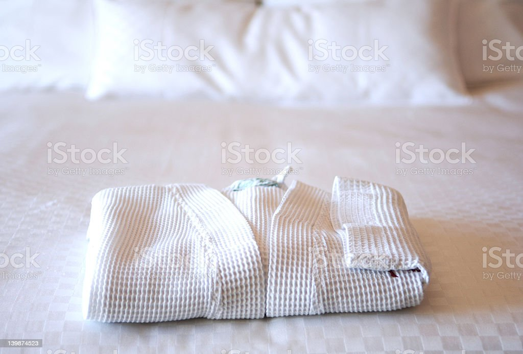 hotel bed with white bathrobe stock photo