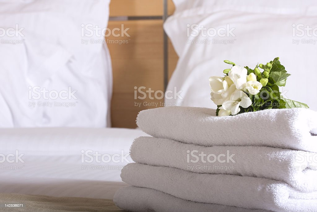 Hotel bed with white linen, towels and posy of flowers stock photo