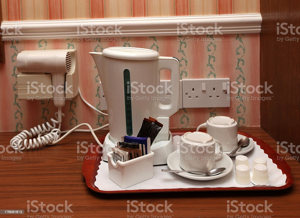 Hotel bedroom complimentary tea and coffee tray with hair dryer royalty-free stock photo