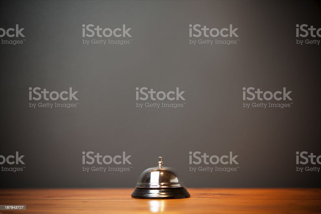 Hotel bell isolated on wooden table stock photo
