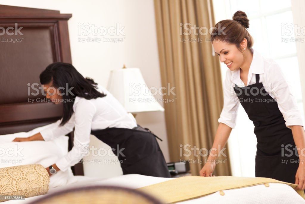 Hotel cleaning staff setting up a room for guests stock photo