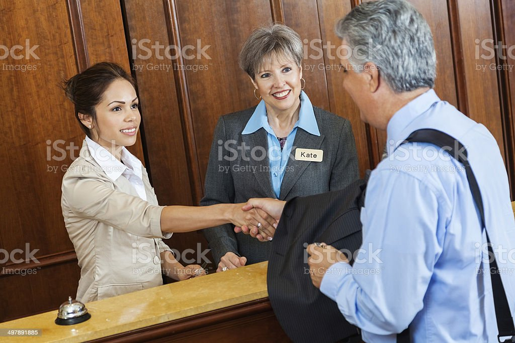 Hotel clerk and manager shaking hands with customer stock photo