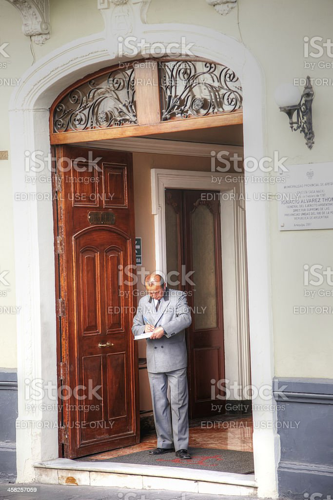 Hotel concierge in doorway writing on clipboard royalty-free stock photo