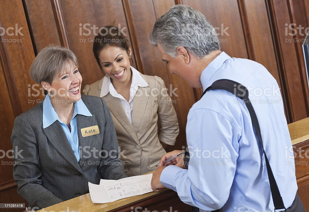 Hotel front desk workers discussing stay and bill with guest royalty-free stock photo