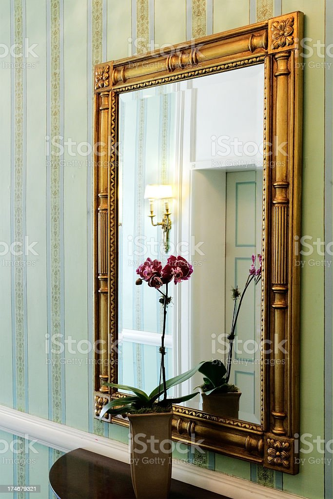 Hotel hallway interior with gold framed mirror and flower stock photo