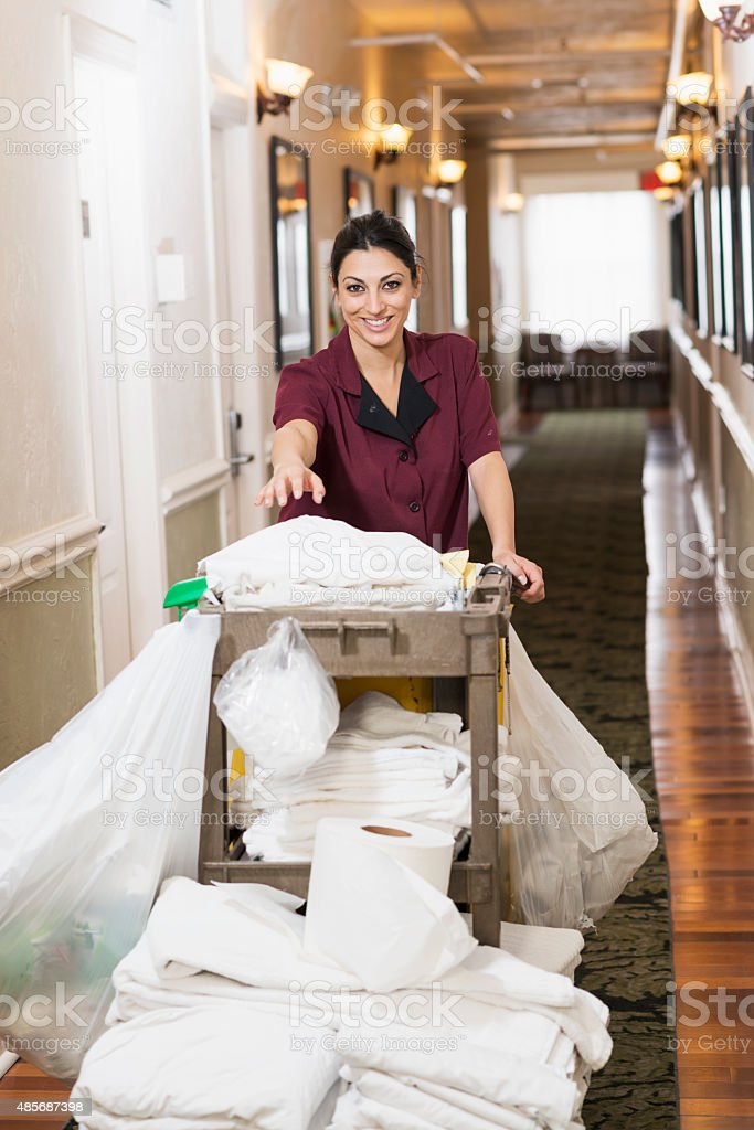Hotel housekeeper pushing cleaning cart down hallway stock photo