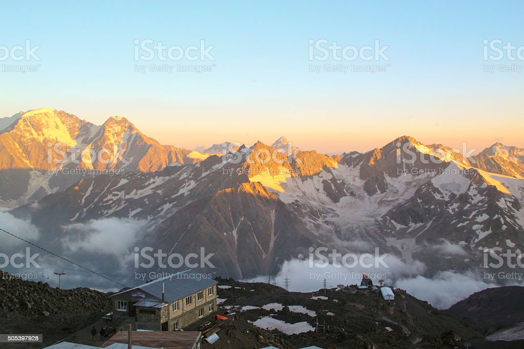 Hotel in the mountains illuminated by the setting sun stock photo