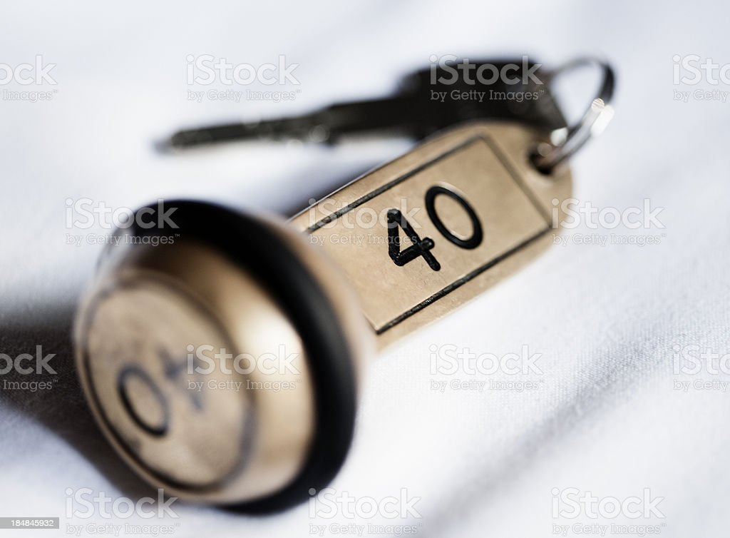 Hotel key lying on the room's bed. stock photo