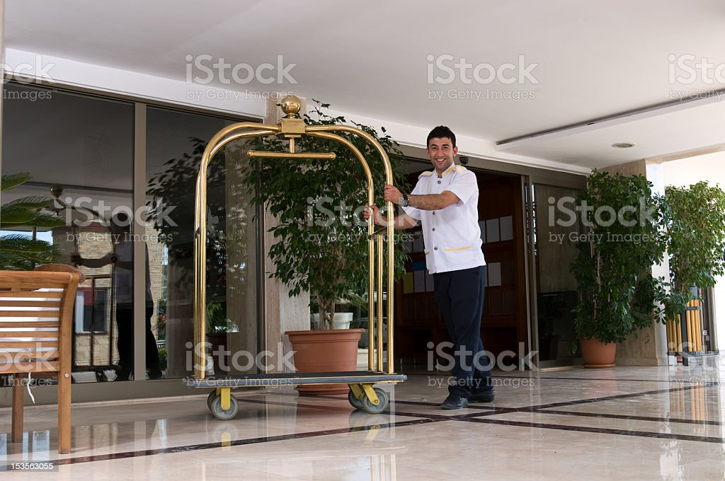 Hotel lobby and bellman holding a luggage cart stock photo