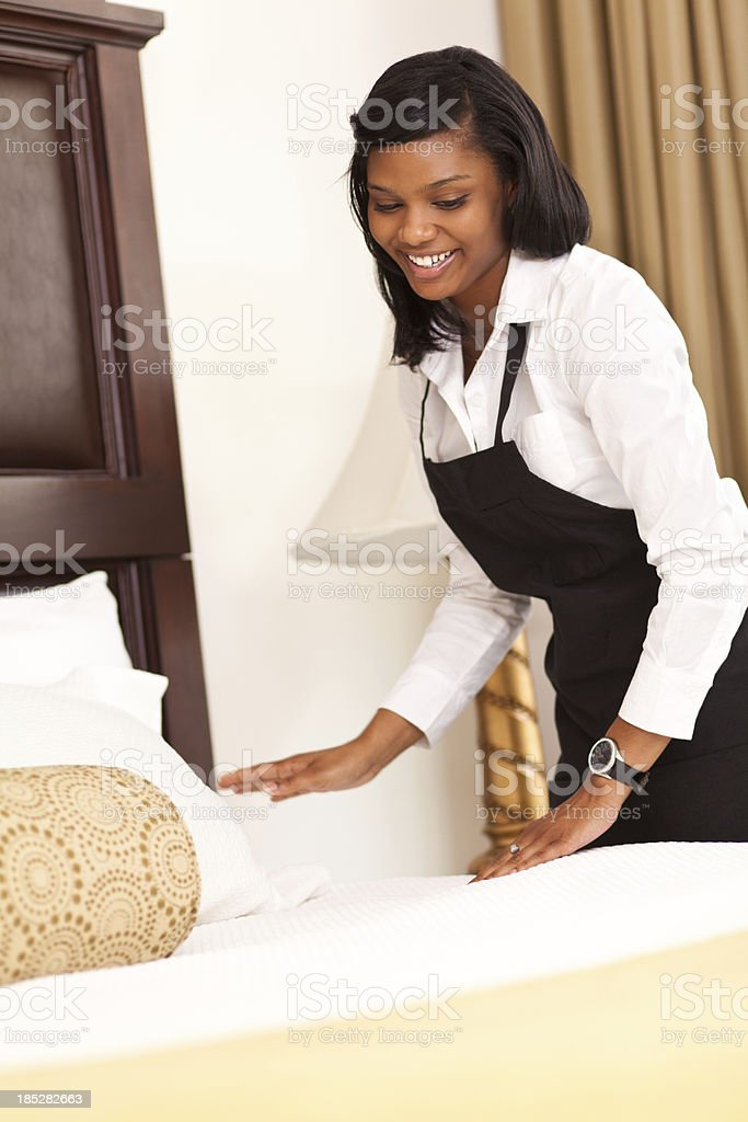 Hotel maid making up a bed for guests royalty-free stock photo
