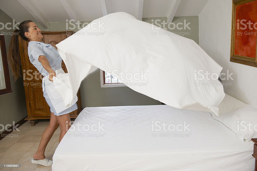 Hotel maid putting throwing sheet on bed stock photo