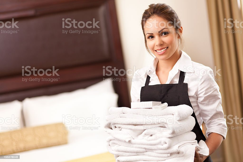Hotel maid with towels in guest room stock photo