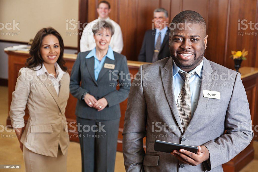 Hotel manager holding tablet with service team stock photo