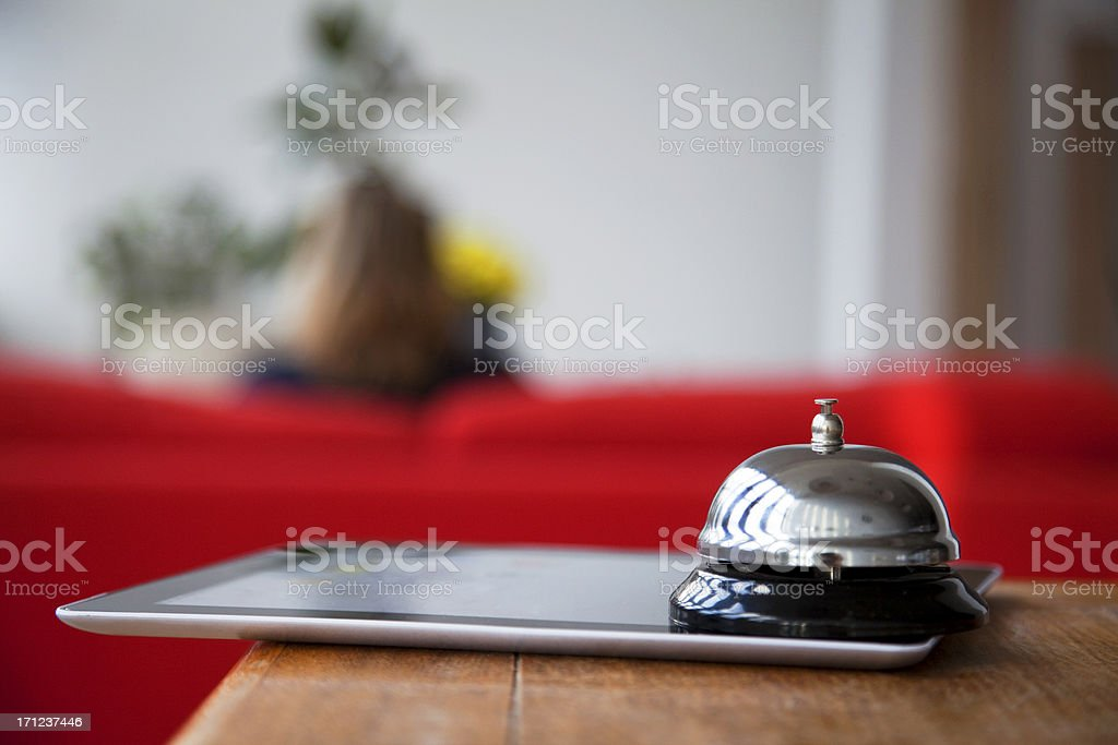 Hotel reception desk with bell on mobile tablet royalty-free stock photo