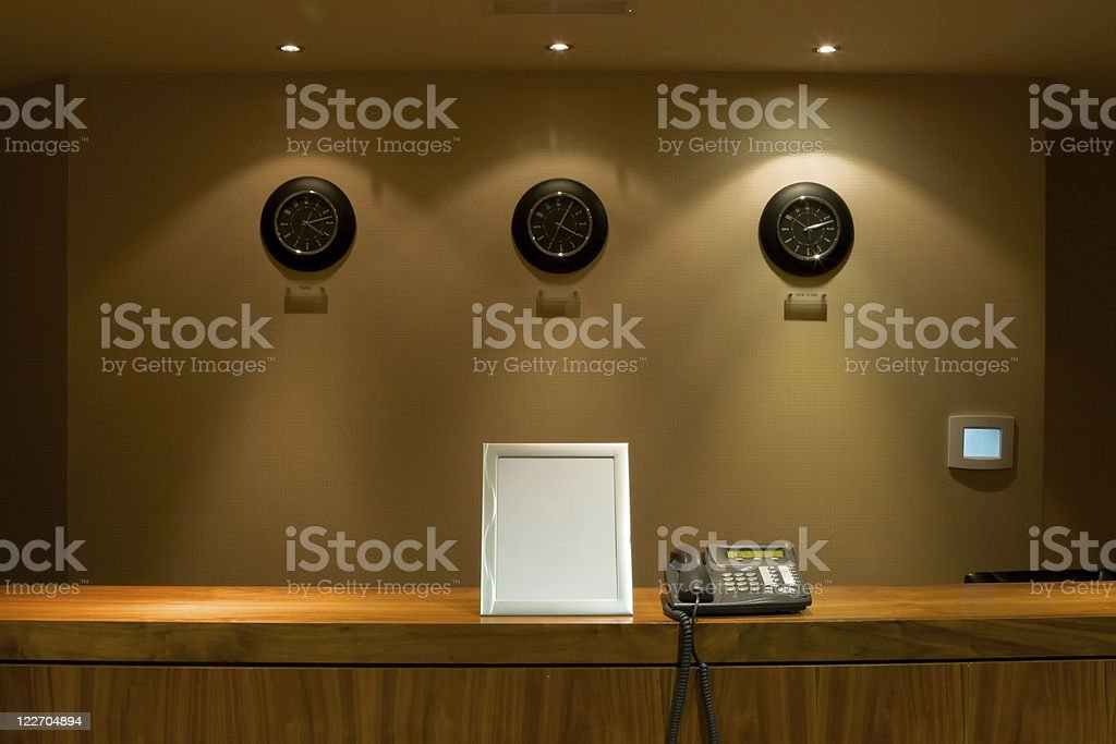 hotel reception desk with phone and signboard stock photo