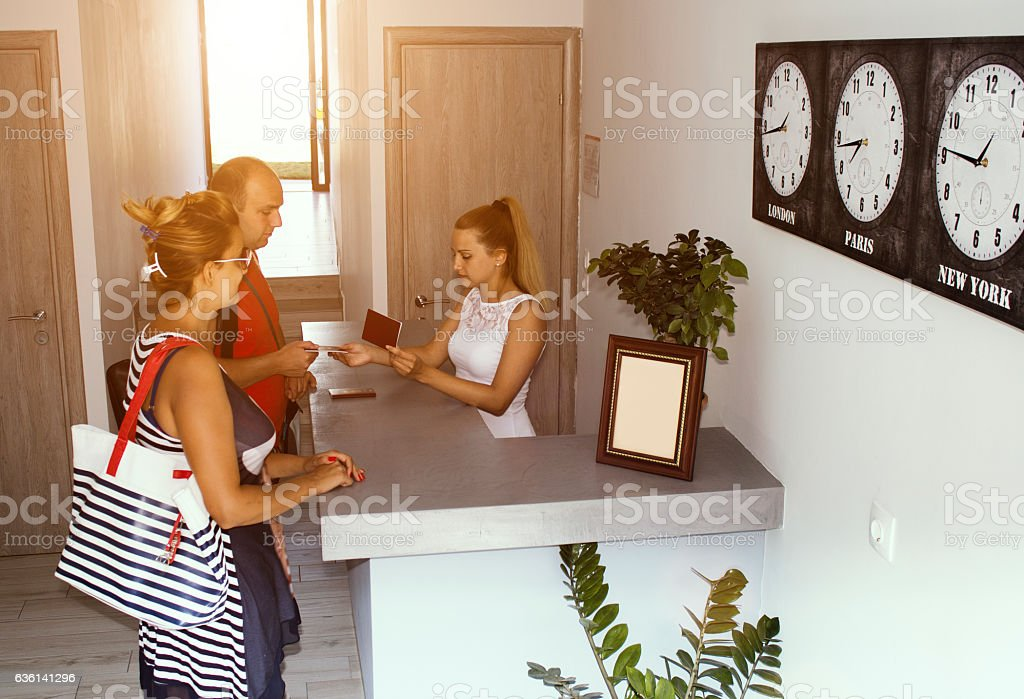 Hotel receptionist checking couple in stock photo