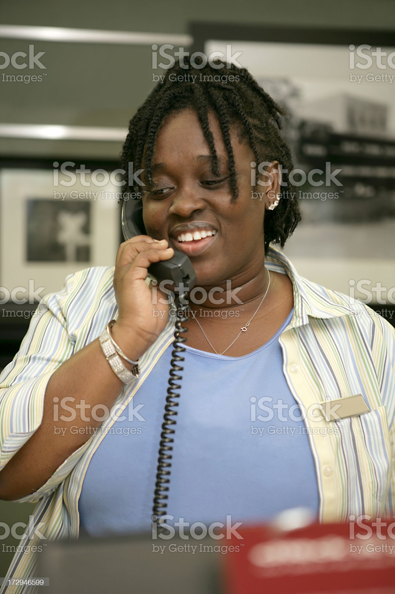 Hotel receptionist happily answering a phone call royalty-free stock photo