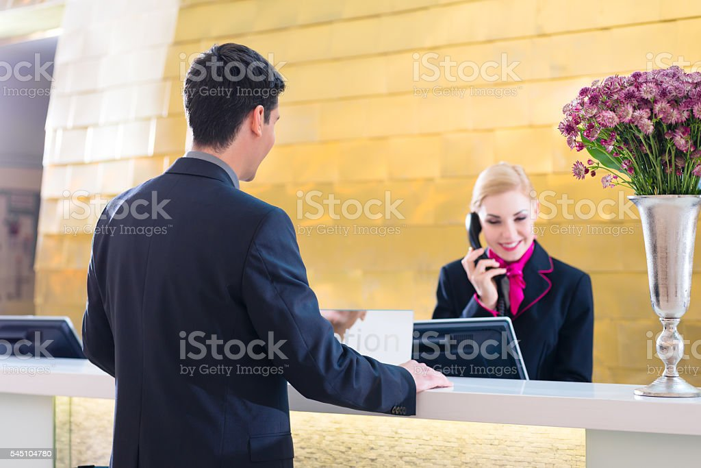 Hotel receptionist with phone and guest stock photo