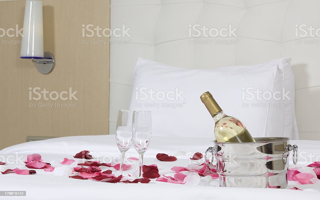 hotel room with big bed and red flowers stock photo