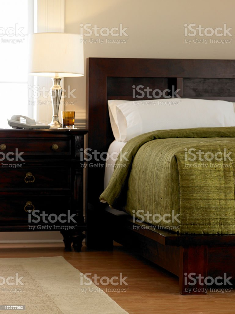 Hotel room with dark wood furniture and green bedding royalty-free stock photo