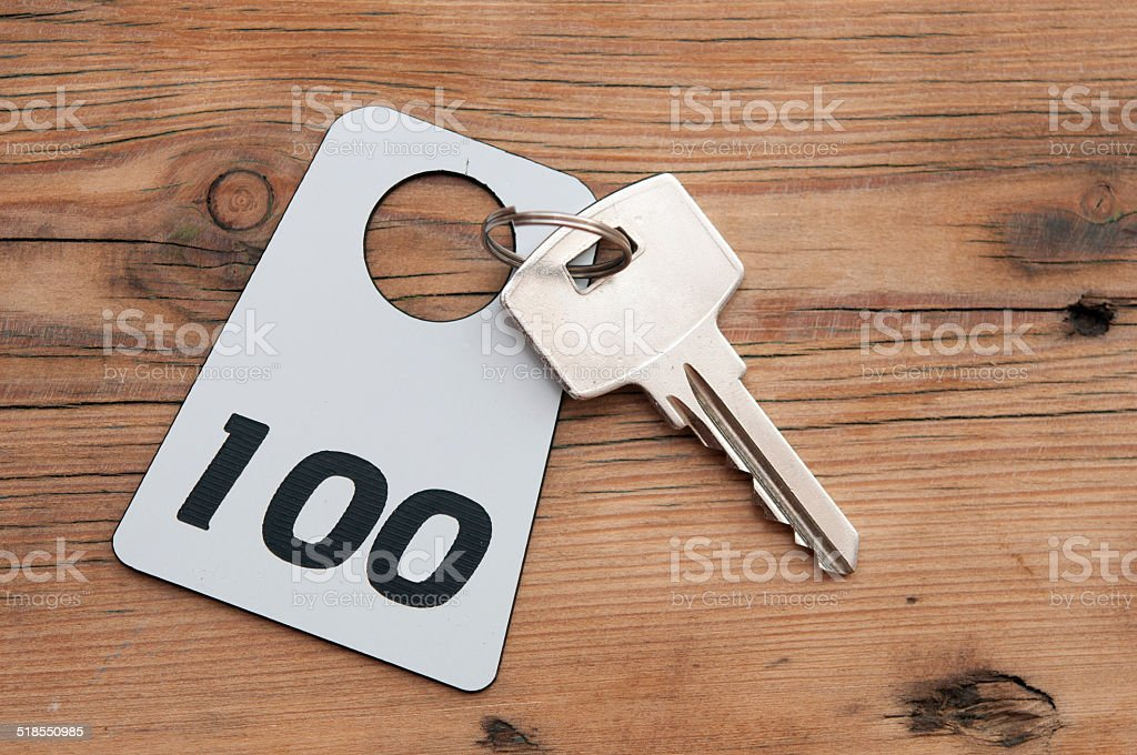 Hotel suite key with room number 100 on wood table stock photo