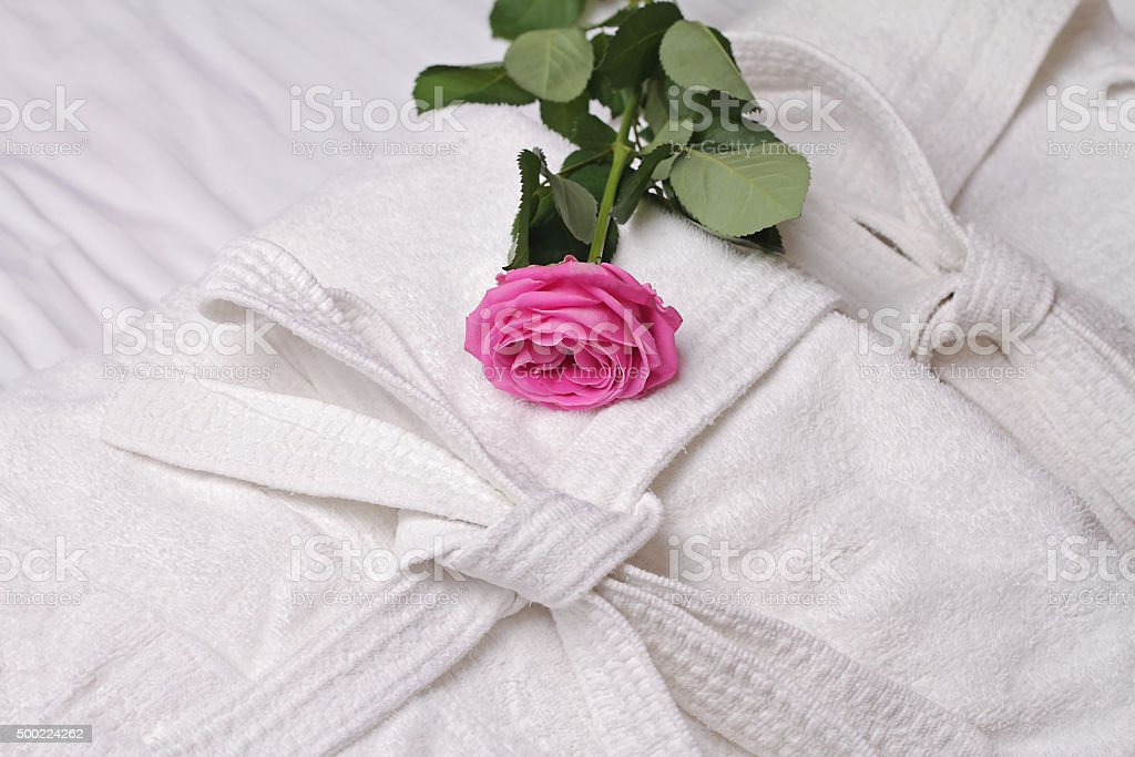 Hotel towels and bathrobe decorated with rose flower stock photo