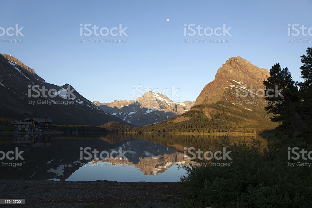 Hotel with Swiftcurrent Lake and mountain reflections Glacier NP stock photo