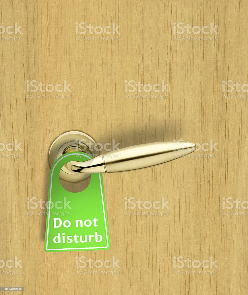 Hotel wood door with a Do not disturb sign stock photo