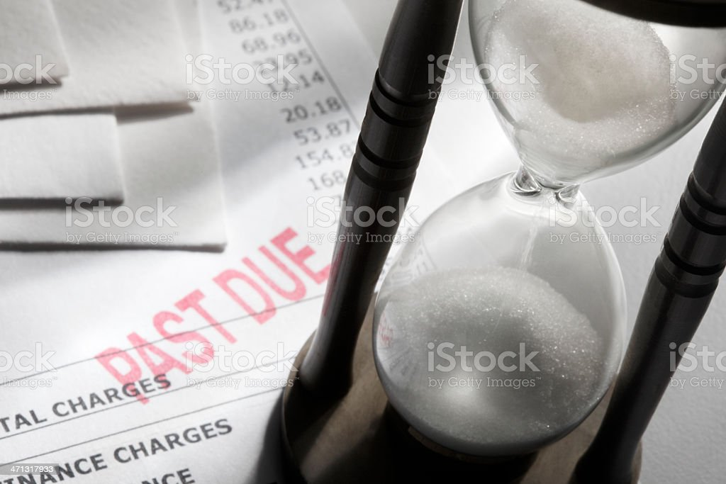 Hour glass sitting on a past due invoice. stock photo