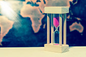 Hourglass against grunge world map