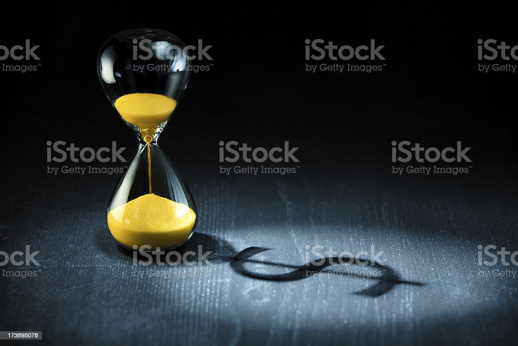 Hourglass and dollar shadow stock photo