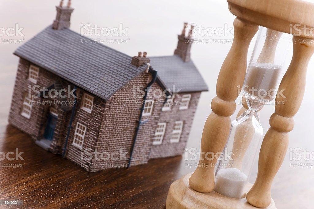 Песочные часы и дом недвижимости Концепция Стоковые фото Стоковая фотография