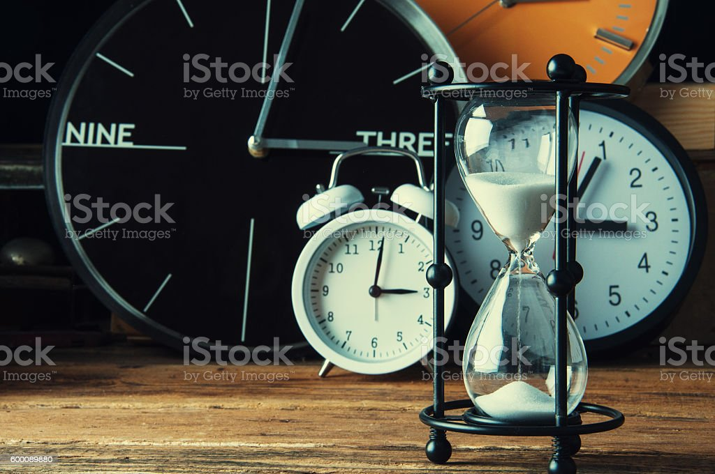 Hourglass and ticking clocks on old wooden table stock photo