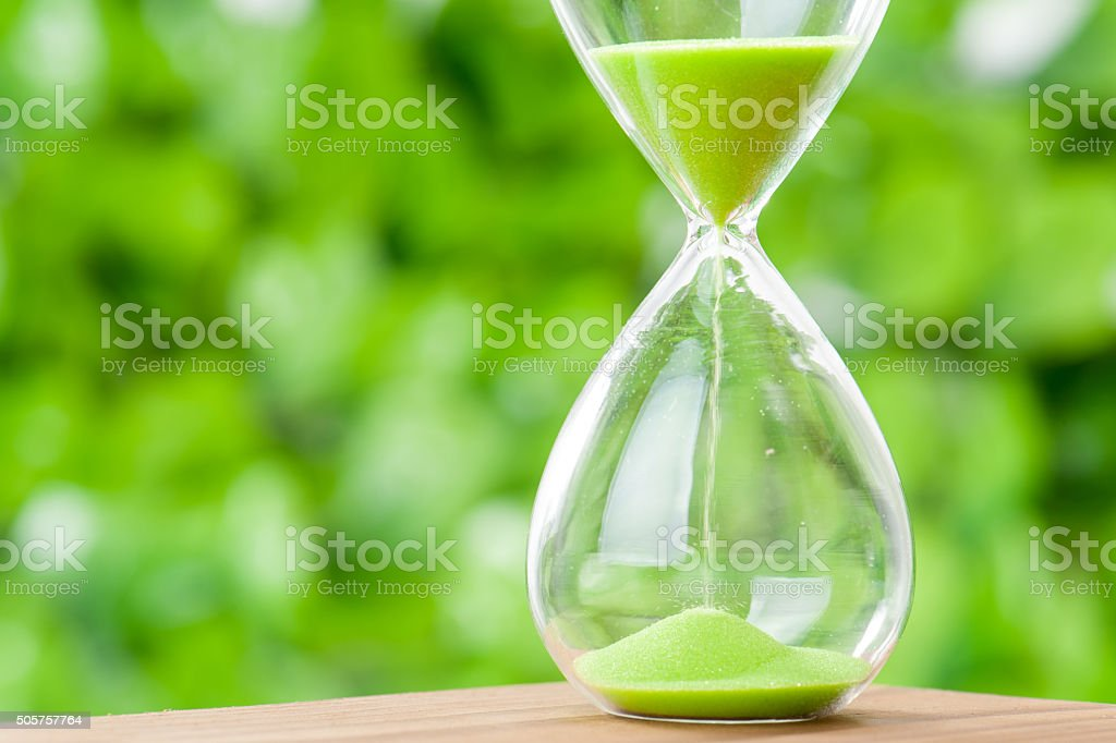 Hourglass, green background stock photo