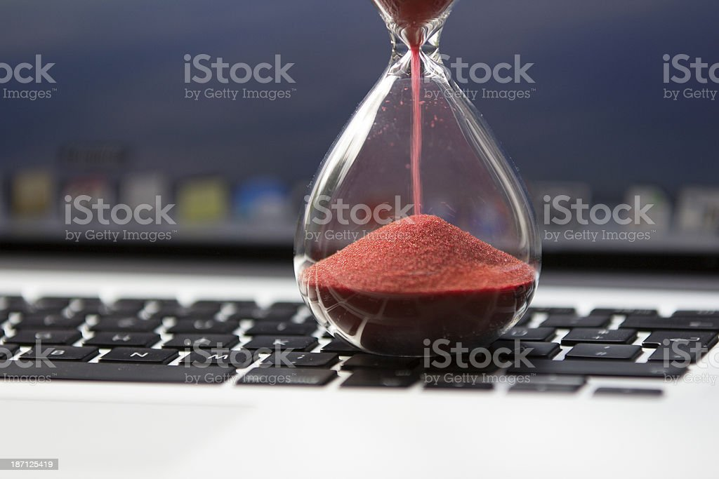 Hourglass on computer keyboard stock photo