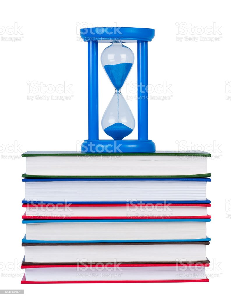 Hourglass on pile of books isolated white background. royalty-free stock photo