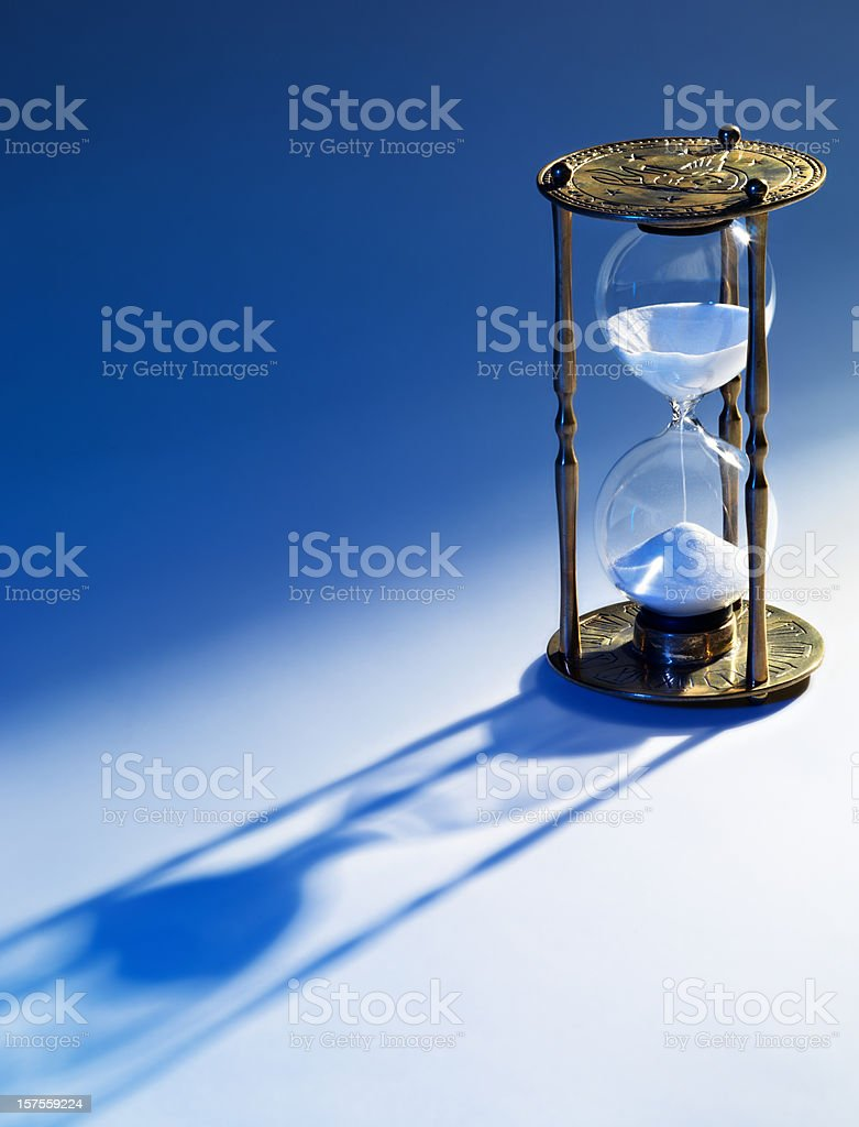 Hourglass, Time running out, blue background royalty-free stock photo