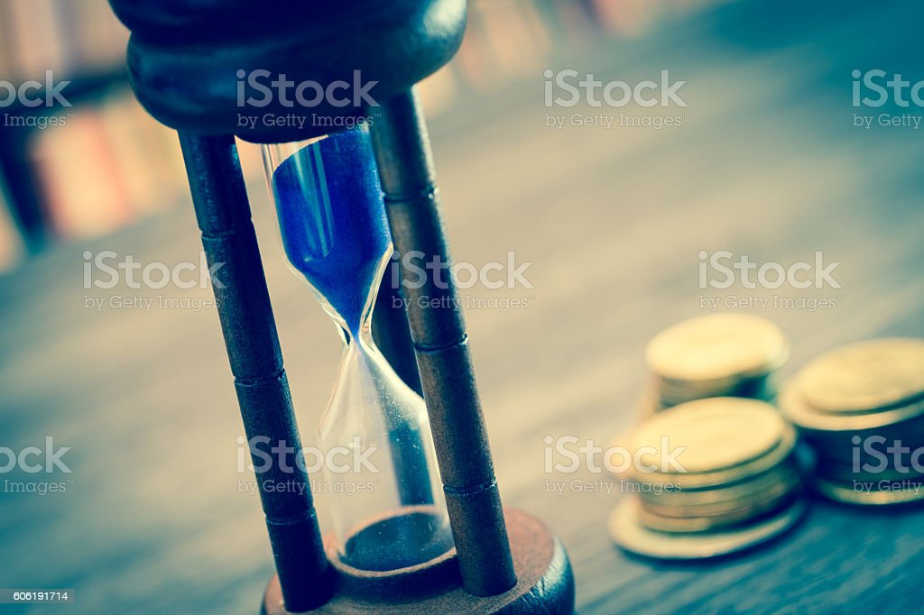 Hourglass with coins stock photo
