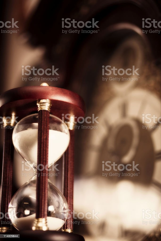 Hourglass with out of focus clockface in background, vertical royalty-free stock photo