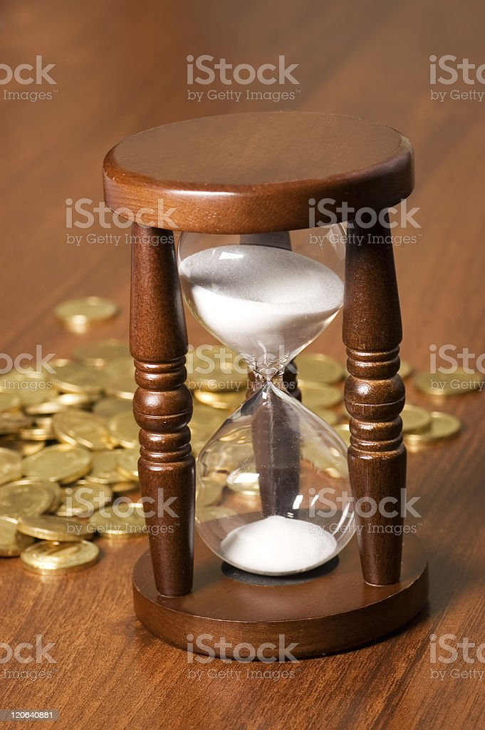 Hourglasses and coin On a wooden table royalty-free stock photo