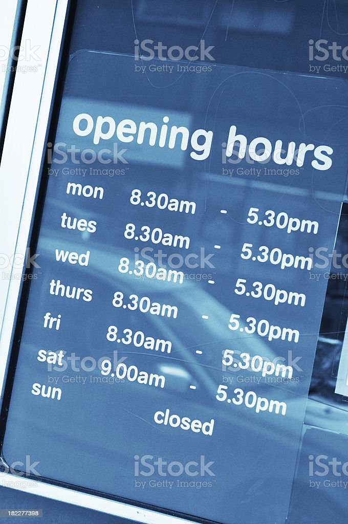 Hours of operation on window of a business stock photo