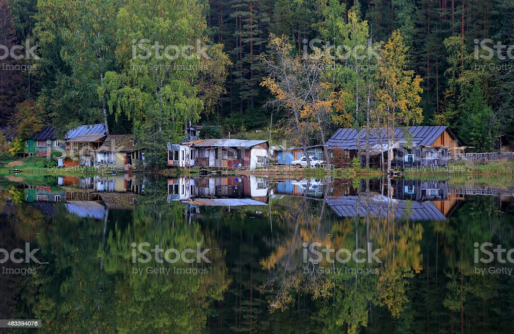House and autumn forest on the lake stock photo