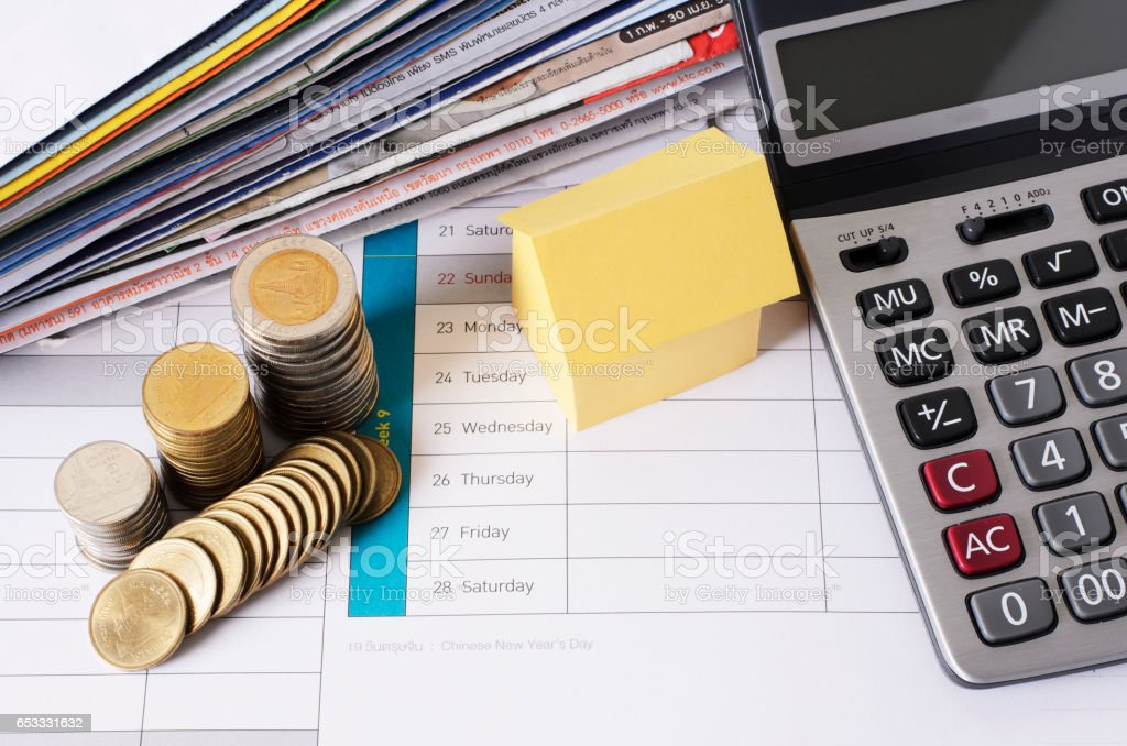 house and coin stack with calculator and bill payment for loan money concept stock photo
