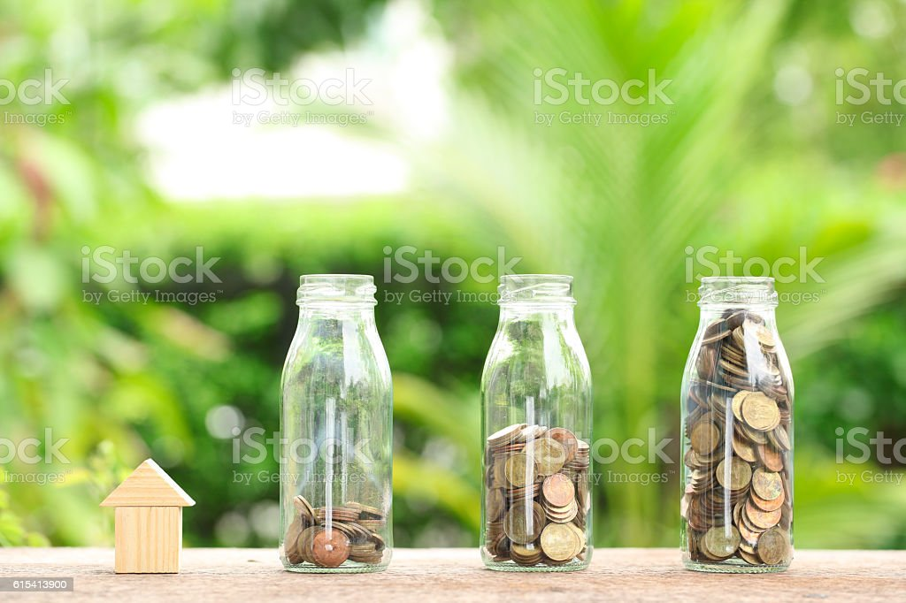 House and coins in jar. stock photo