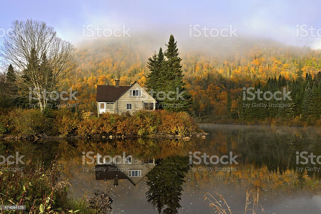 House and forest in autumn with reflections in a pond stock photo
