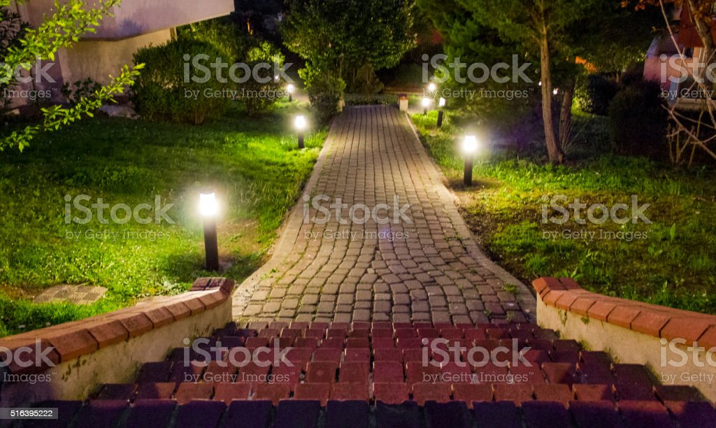 House and garden in city at midnight stock photo