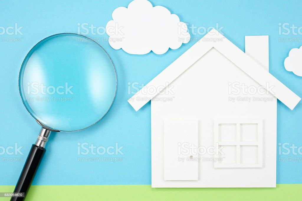 House and magnifier on paper background. stock photo