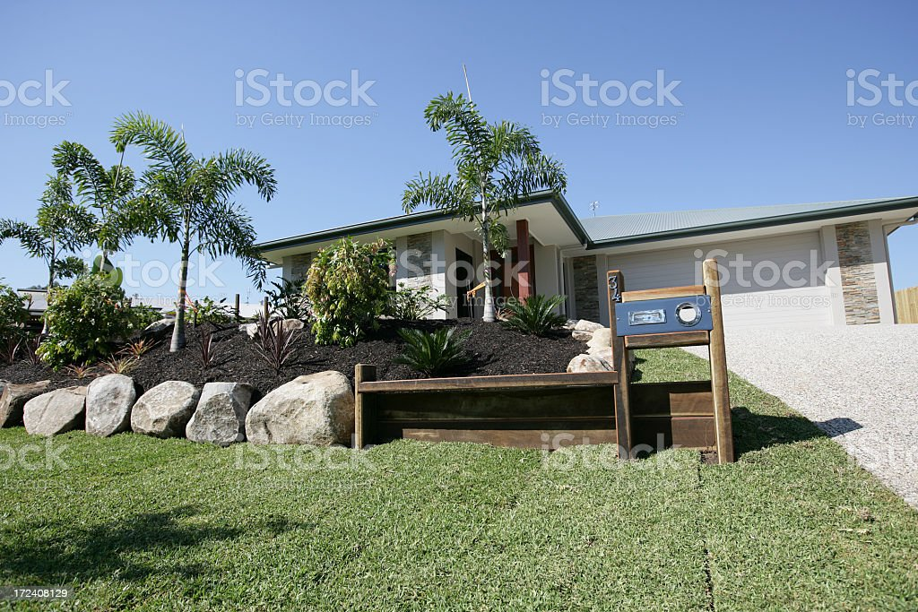 A house and manicured front lawn with rock landscaping royalty-free stock photo