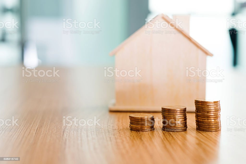 House and stacks of coins stock photo